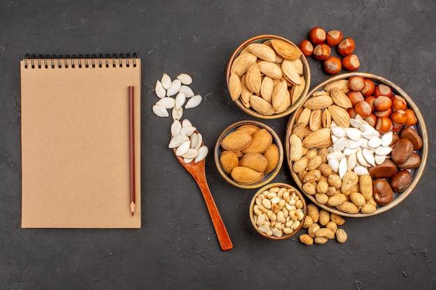 暗い表面の鉢の中のさまざまなナッツの新鮮なナッツの上面図