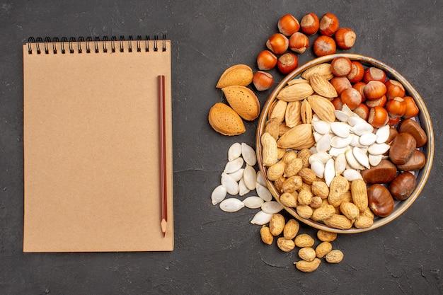 暗い表面のトレイ内のさまざまなナッツの新鮮なナッツの上面図