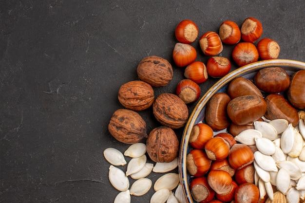 灰色の表面のトレイ内のさまざまなナッツの新鮮なナッツの上面図