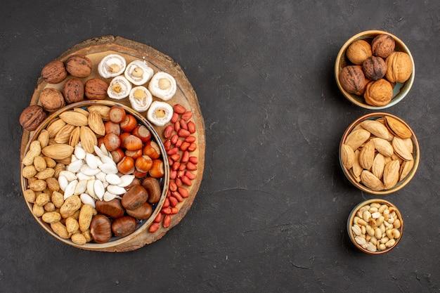 Вид сверху разных орехов с белыми конфитюрами на серой поверхности