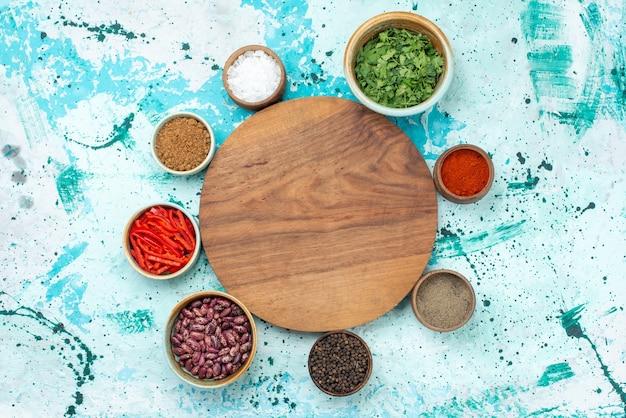 Вид сверху различных приправ с перцем, фасолью и зеленью на голубом столе, острый острый ингредиент для перца