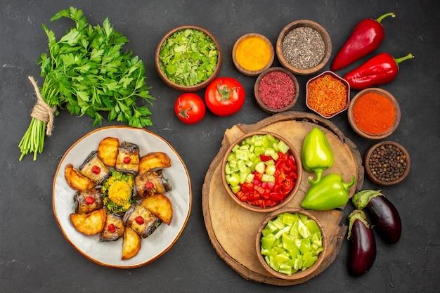 Вид сверху различных приправ со свежими овощами на черном столе