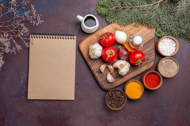 黒に新鮮な野菜を使ったさまざまな調味料の上面図