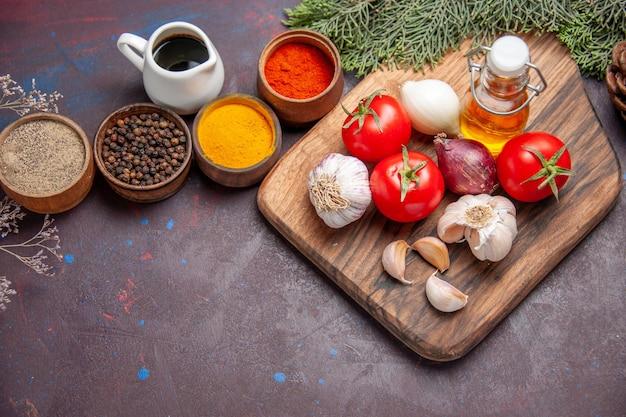 黒に新鮮な野菜を使ったさまざまな調味料の上面図 無料写真