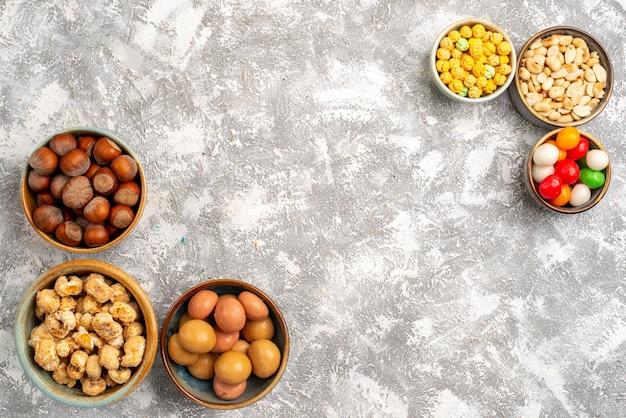 白い表面上のさまざまなスナックナッツとキャンディーの上面図