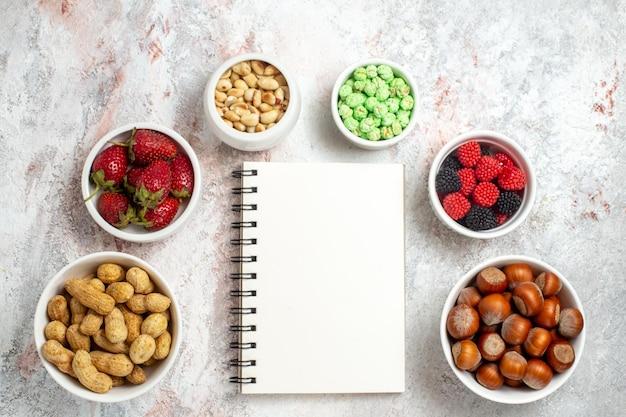 白い表面上のさまざまなスナックピーナッツヘーゼルナッツとキャンディーの上面図