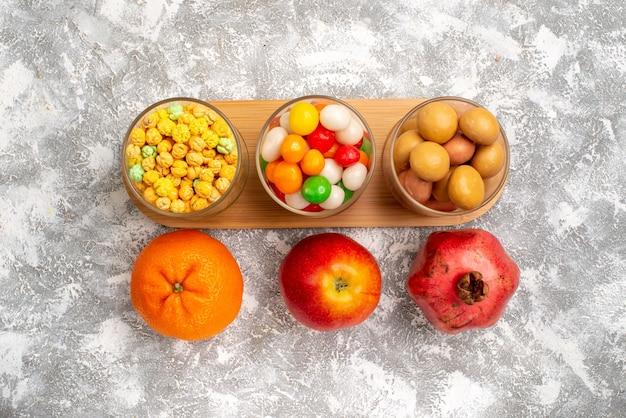 白い表面に果物とさまざまな甘いキャンディーの上面図