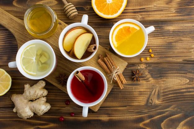 Вид сверху разных чаев в белых чашках на деревянном фоне
