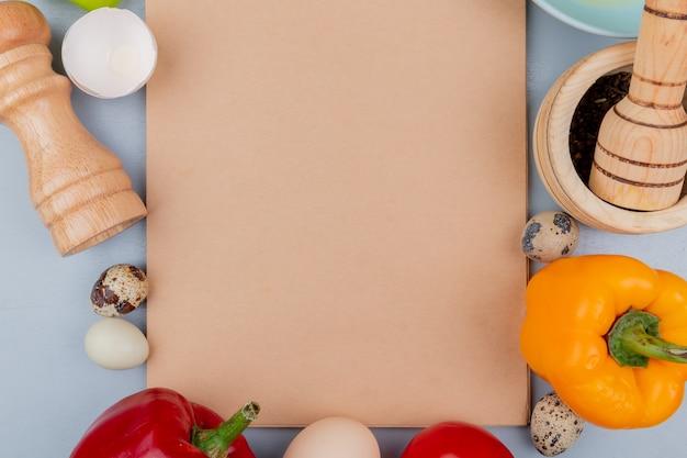 コピースペースと白い背景の上のピーマンとチキンとウズラの卵などのさまざまな種類の卵のトップビュー