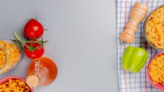 さまざまな種類のパスタのcavatappiパイプリガートなどの平面図と格子縞の布にトマトバターコショウの塩とコピースペースを持つ青い表面