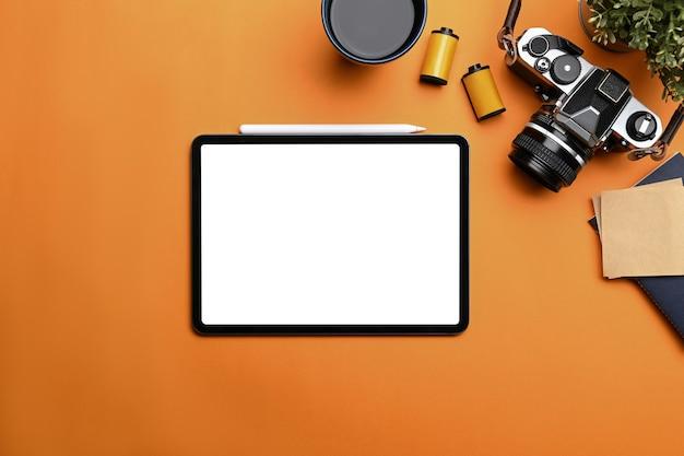 사진작가 작업장의 주황색 배경에 있는 디지털 태블릿, 카메라, 커피 컵, 노트북의 상위 뷰.