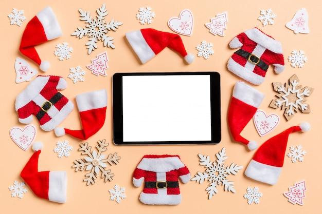 クリスマスの装飾とサンタ帽子とデジタルタブレットの平面図です。幸せな休日の概念