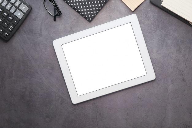 Вид сверху цифрового планшета с офисными поставщиками на столе