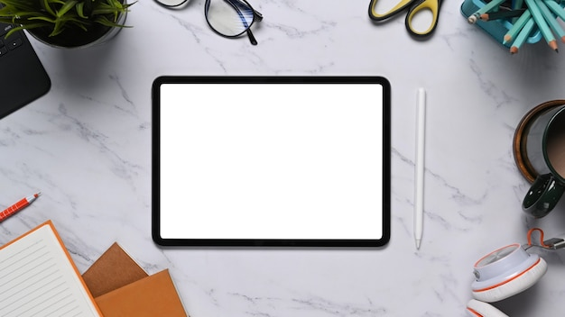 Вид сверху цифрового планшета с белым экраном, окруженным канцелярскими принадлежностями, наушниками и записной книжкой на мраморном столе.