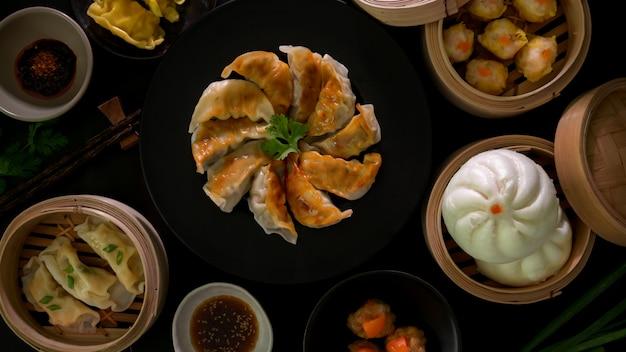 点心の平面図、黒皿に餃子、餃子、卵のポークボールとパン