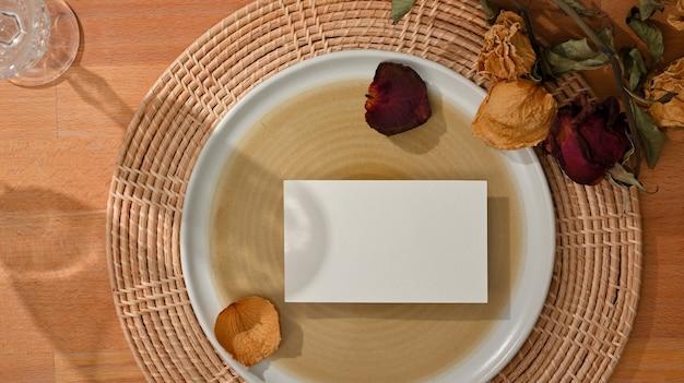 Вид сверху на обеденный сервиз с макетом визитной карточки на макете керамической тарелки и цветком, украшенным на столе