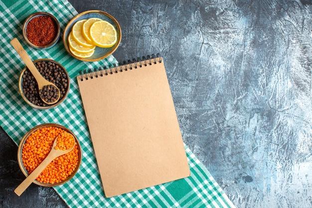 暗いテーブルの上のさまざまなスパイス イエロー エンドウ豆とスパイラル ノートとディナーの背景の平面図