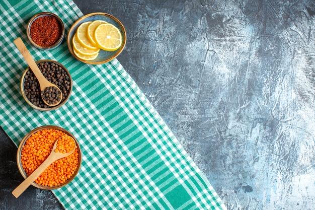 暗いテーブルの上の緑の剥かれたタオルにさまざまなスパイス イエロー エンドウ豆を使ったディナーの背景のトップ ビュー