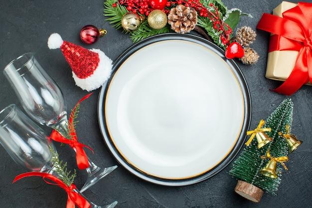Вид сверху на обеденную тарелку рождественской елки еловые ветки хвойные шишки подарочная коробка шляпа санта-клауса упавшие стеклянные кубки на черном фоне