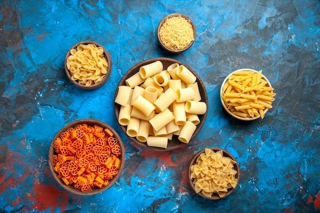 青の背景にさまざまなサイズの鍋にパスタ ヌードルを使った夕食の準備のトップ ビュー