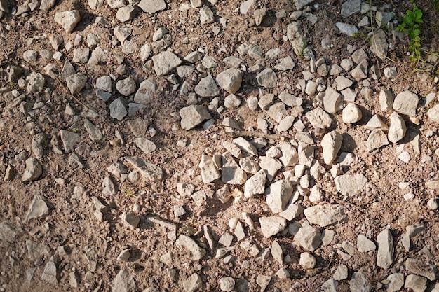 Вид сверху фрагмента грунтовой дороги. сухая земля с камнями. абстрактный естественный текстурированный фон. камни и галька на земле.