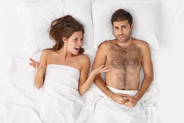 실망한 여성의 상위 뷰는 침대에서 남편과 분쟁, 실패에 대한 비난, 다툼 및 제스처를 적극적으로 수행합니다. 부부는 수면 전에 관계를 정리하기 전에 논쟁을 벌입니다. 가족, 갈등