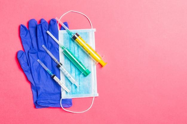 일회용 수술 마스크, 라텍스 의료 장갑 쌍 및 분홍색 배경에 주사기의 상위 뷰. 복사 공간 바이러스 보호 개념입니다.