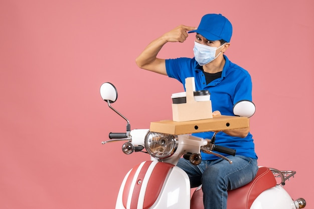 Вид сверху на разочарованного доставщика-мужчину в маске в шляпе, сидящего на скутере и показывающего заказы на пастельно-персиковом фоне