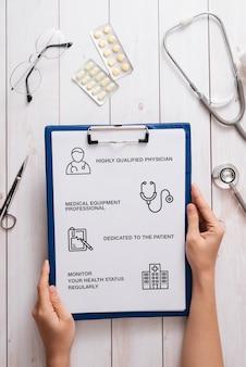 クリニック/病院の医療機器を備えたドクターデスクの上面図。コピースペースのある白い表面に聴診器、処方クリップボード、錠剤のボトル。ヘルスケアと医療の概念。