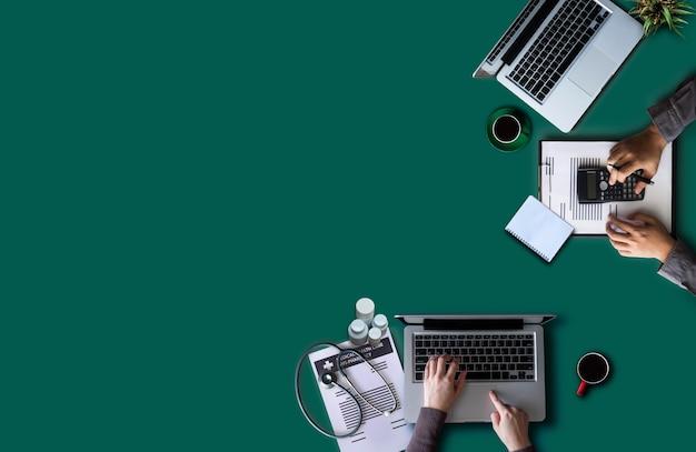 手書き部門が一緒に働いている医師の上面図は、メモを書き、計算機を使用して経費を計算します-木製のテーブルの収入。