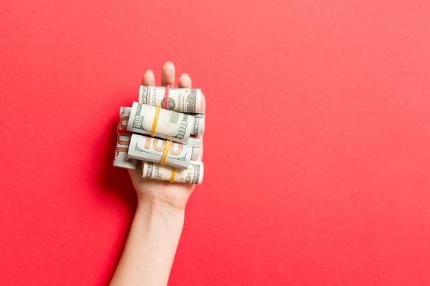 다채로운 표면에 여성 손에 튜브에 달러 지폐의 상위 뷰