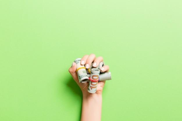 Вид сверху долларовых купюр, свернутых в трубочки в женской ладони на зеленом фоне. пенсионное понятие.