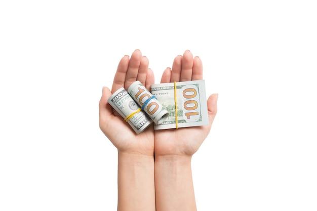 Вид сверху долларовых купюр, свернутых в трубки в женских ладонях на белом изолированном фоне. пенсионное понятие.