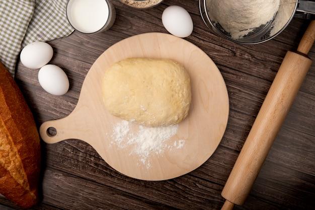 Вид сверху теста и муки на разделочную доску с яйцом молочной скалкой на деревянном фоне