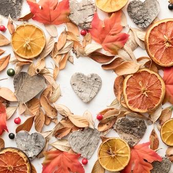 Вид сверху сушеных цитрусовых с осенними листьями и в форме сердца