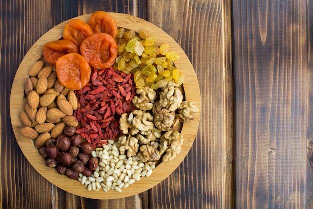 Вид сверху сухофруктов и различных орехов на разделочной доске