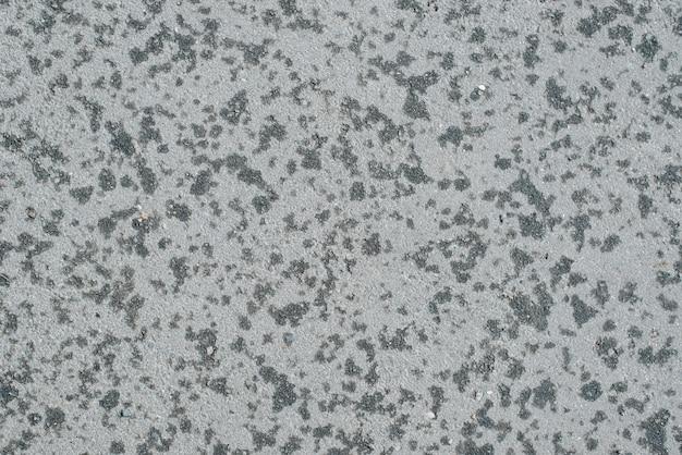 Вид сверху на высохший серый асфальт после дождя, следы капель воды на шероховатой каменной поверхности