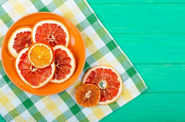 コピースペースを持つ緑の木製の背景に格子縞のテーブルクロスのプレートで乾燥したオレンジとグレープフルーツのスライスのトップビュー
