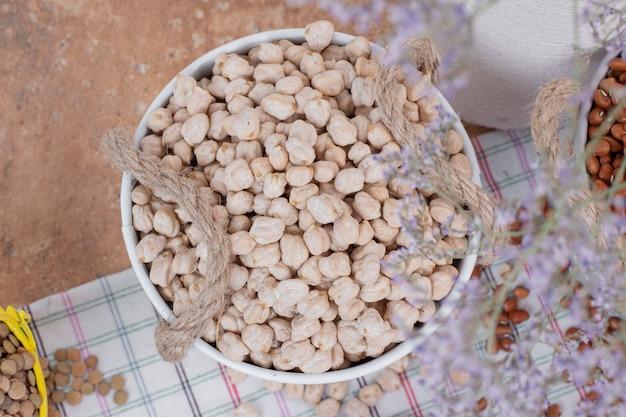 花とバケツの乾燥エンドウ豆の上面図。