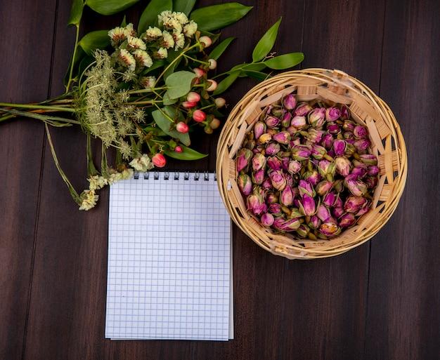 コピースペースを持つ木材にさまざまな花とバケツに乾燥したバラのつぼみの平面図