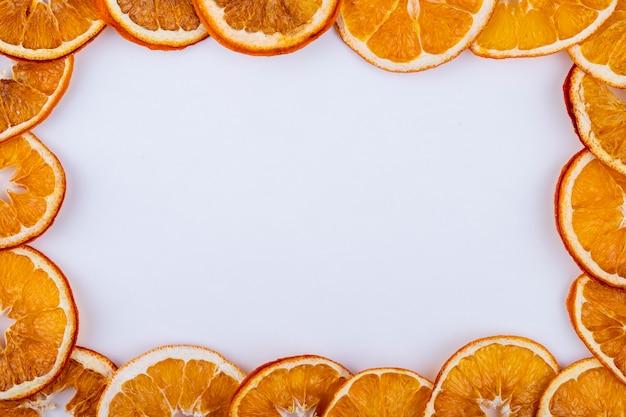 コピースペースと白い背景の上に配置されたオレンジの乾燥スライスのトップビュー