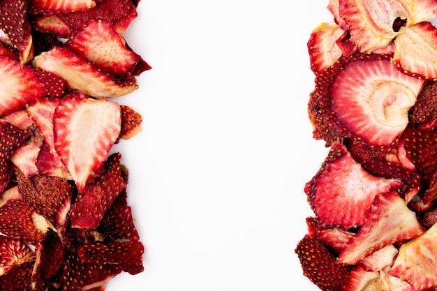 コピースペースと白い背景の上に配置された乾燥イチゴのスライスのトップビュー
