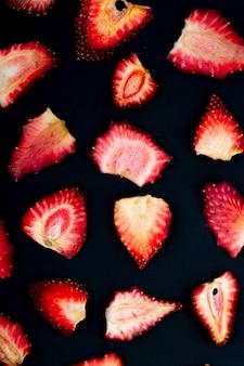 黒の背景に分離された乾燥したイチゴのスライスのトップビュー