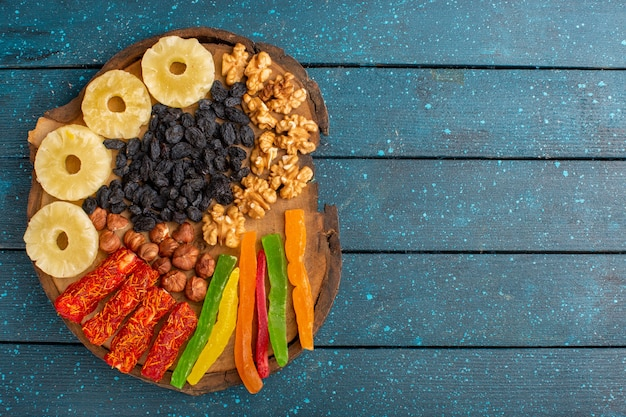 Вид сверху сушеных сладких фруктов ананасовых колец, грецких орехов и нуги на синей поверхности
