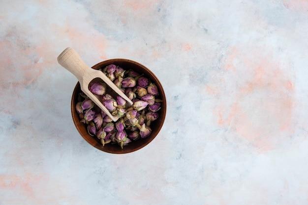 흰색 표면 위에 나무 그릇에 마른 꽃의 상위 뷰