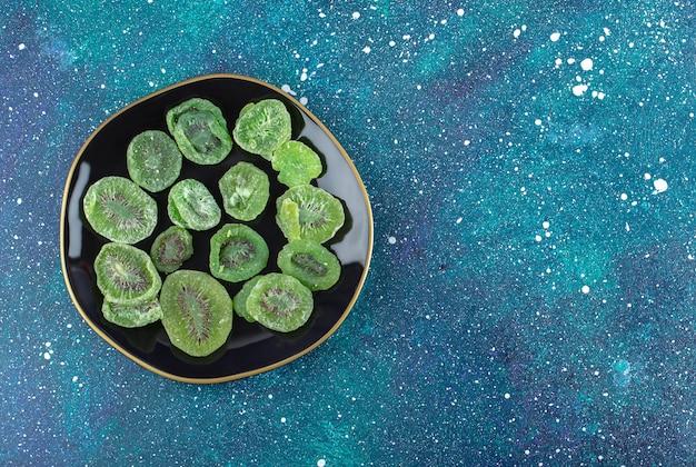 Вид сверху сухих ломтиков киви на черной тарелке.