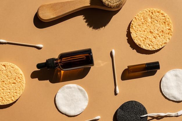 ドライマッサージアクセサリーと化粧品の上面図。環境にやさしいゼロウェイスト化粧品のコンセプト。天然木のフェイスブラシ、コットンパッド、イヤースティック、ダークガラスのボトルに入った美しいエッセンシャルオイル。