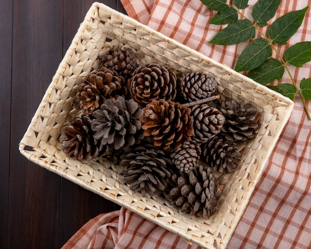 Вид сверху сухих сосновых шишек на корзине с листом на проверенной скатерти и дереве