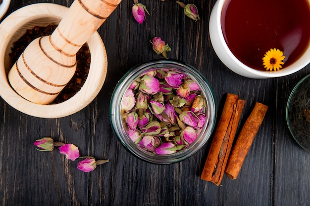 シナモンスティックと木造モルタルが黒い胡椒と黒い木のお茶でいっぱいのガラスの瓶に乾燥したバラのつぼみの平面図