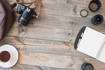Top view of dslr camera; cup of tea; spiral notepad; pen; camera lens and bag on wooden table